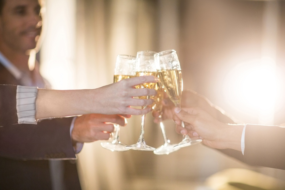 Close-up of group of businesspeople toasting glasses of champagne in the office