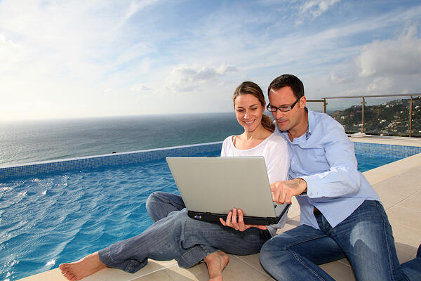 Happy Couple Using Laptop By Swimming Pool