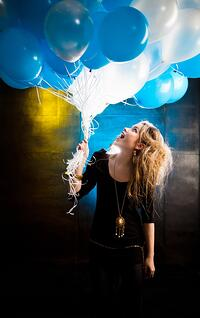 Happy girl holding a bunch of hot-air balloons