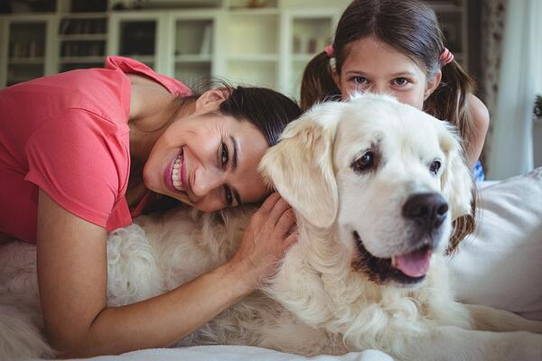 Mother and daughter sitting with pet dog in living room at home