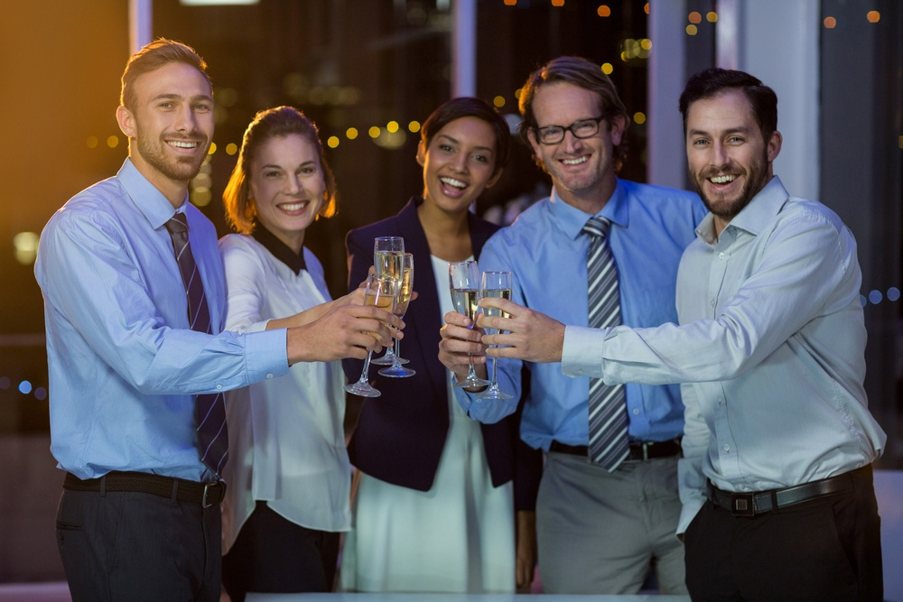 Portrait of Business People Toasting Glasses of Champagne in Office at Night
