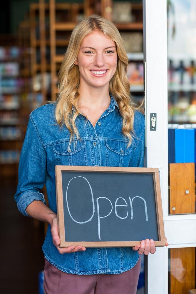 Portrait of smiling owner holding open signboard in supermarket.jpeg
