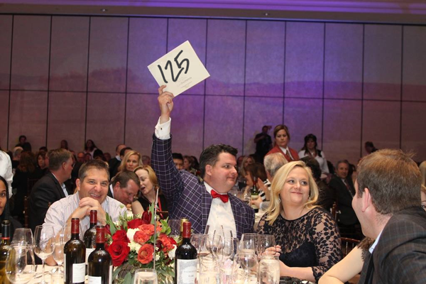 Bidder holding up bid card at a fundraiser